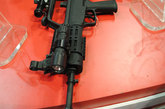 """95-1式(出口型为97A)进行了大量改进工作,取消了前方小握把,以利于枪挂榴弹发射器的加装及与枪匹配协调。上护手的散热孔由原步枪的6个改为5个,各孔的间距相等,孔口适当加大,原后方机匣位置的保险及快慢机整体前移至握把左上方附近,原枪中""""两点式""""枪背带改用""""三点式""""结构。"""