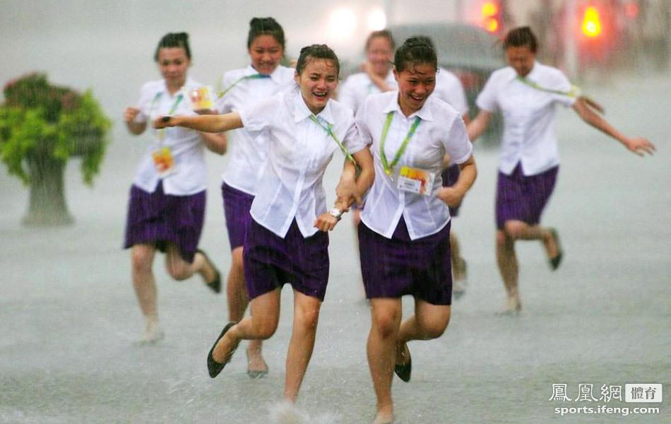 上海,2011游泳世锦赛第16日,当地突降暴雨,志愿者们在雨中奔跑.