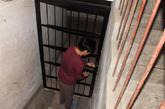 9月22日,河南洛阳,住该门洞的居民在地下室外讲述看到警察解救被囚女子经过。河南洛阳警方近日破获一起发生在地下4米深处的案件———消防兵转业的34岁当地男子李浩在长达两年的时间里,瞒着妻子秘密在外购置一处地下室,耗时1年开挖地窖并将6名歌厅女子诱骗至此囚禁为性奴。本月初,该案因一女子的举报电话而告破。洛阳警方从地窖中成功解救出4名歌厅女,同时,还找到两具尸体。图为9月22日,河南洛阳,住该门洞的居民打开地下室大门。