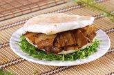 肉夹馍,为啥受欢迎:虽然肉夹馍不是上海本地的美食,不过在上海已经遍地开花,你去看看大学周围就知道了。肉和菜都是自选的,我们喜欢手撕鸡肉搭配香菜、生菜和多一点的辣椒酱,只要5块钱。将蒸好的面饼从中间切开,把美味的肉末和蔬菜末填在里面即可。