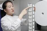 精子库护士宋娟在介绍存放精子标本的容器。她手中的容器一提为12个小盒,而她旁边的大罐子可以存放1万份精子标本,目前由于精子库存少还未启用。