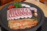 """烤五花肉,在韩国菜式中,烤五花肉应该是最具代表性的。关于烤五花肉的来历,在韩国有2种说法,一种是""""烧酒价格下跌说"""",一种是""""slater说""""。在20世纪60年代的时候,烧酒价格下跌,一般百姓也可以很容易购买酒来喝,但是没有好的下酒菜。因此选择了价格比较便宜的猪肉来做下酒菜。""""slater说""""指当时的建筑工人使用建筑材料slater来烤五花肉,后来传开了。"""