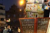 """前往大三巴景点会途经一条热闹拥挤的街道,路两边全是手信店和各种小吃店。瞧这家店铺卖的饮料名字""""波霸奶茶""""还真是搞笑。"""