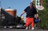 """美国人沃伦(Wesley Warren Jr)本身是个133公斤重的大汉,但现在巨上加巨。因为他的睾丸严重肿胀,重达44.5公斤( 98磅),无法正常生活。他现正筹款100万美元做手术。47岁的沃伦下体异常,令他没法穿牛仔裤和普通裤子,只能把连帽上衣当裤穿,袖子变裤脚,帽子则""""袋""""着睾丸。"""