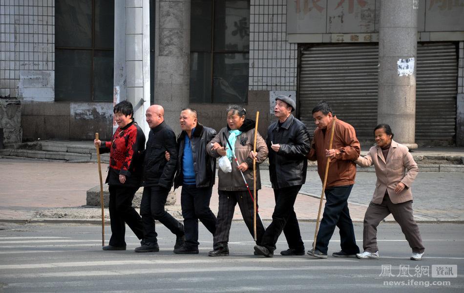 3月29日,在吉林省吉林市青岛街与解放大路交汇处,7名盲人手挽手相互