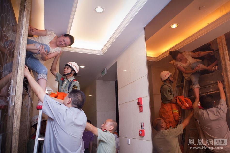 7月7日,南坪某小区,消防官兵将电梯上方的墙体打穿后,被困居民成