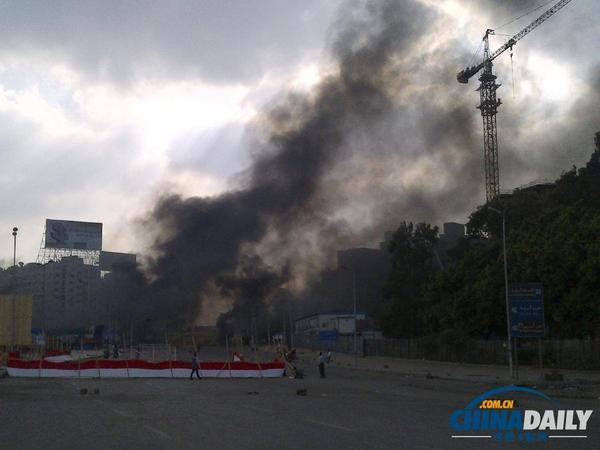 8月14日,位于开罗东北部阿达维耶清真寺外广场前总统穆尔西支持者的营地,埃及安全人士与支持者发生冲突,黑烟从现场升起。